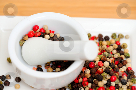 Red Green And Black Peppercorns stock photo, Peppercorns in various colors of red, green and the familiar black peppercorn on white with a Mortar and Pestle by Lynn Bendickson