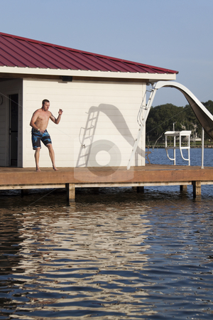 Dock Man stock photo, A man is doing a back flip off the end of a dock into the water by Kevin Tietz