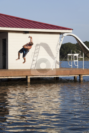 Back Flipper stock photo, A man is doing a back flip off the end of a dock into the water by Kevin Tietz
