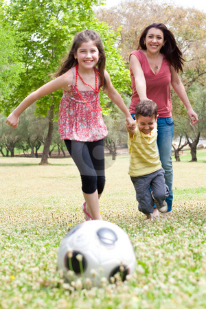 Childrens playing soccer with their mother stock photo, Childrens playing football with their mother in the park by Get4net