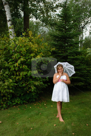 Preteen Girl Outside stock photo, A young preteen girl is walking outside in a white dress while holding a lacy umbrella. by Richard Nelson
