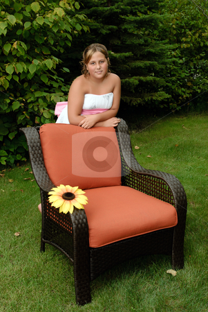 Girl Relaxing In The Sun stock photo, A cute young girl, wearing a white dress is relaxing in the sun whilte leaning on a wicker chair outside. by Richard Nelson
