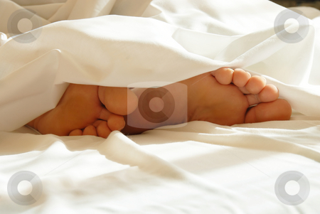Feet in bedding stock photo, Two male feet in white bedding closeup by Julija Sapic