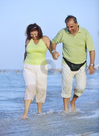 Happy seniors couple  on beach stock photo, Happy senior mature elderly people couple have romantic time on beach at sunset by Benis Arapovic