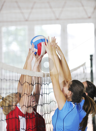 Girls playing volleyball indoor game stock photo, Volleyball game sport with group of young beautiful  girls indoor in sport arena by Benis Arapovic
