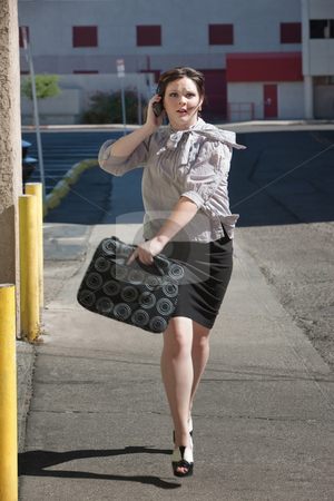 Working woman runs down street. stock photo, Woman is running down street late for meeting. by Scott Griessel