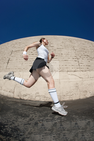 Woman sprints towards the finish line. stock photo, Woman runner practices sprinting towards the fiish line. by Scott Griessel