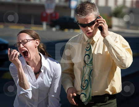 Couple shows displeasure with conversation. stock photo, Couple is upset with people on the opposite end of the line. by Scott Griessel