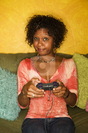 African-American woman plays video game stock photo, Attractive woman plays video game with hand held controllers by Scott Griessel