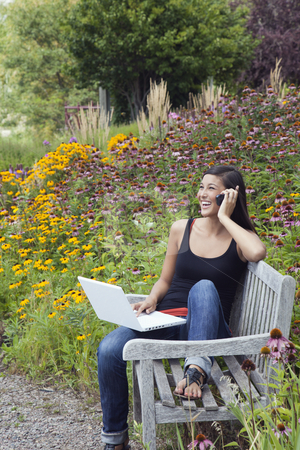 Young Woman Using Laptop and Cellphone on a Park Bench stock photo, Cute young woman laughs while talking on the phone and working on a laptop. She is seated on a park bench amid blooming flowers and trees. Vertical shot. by Edward Bock
