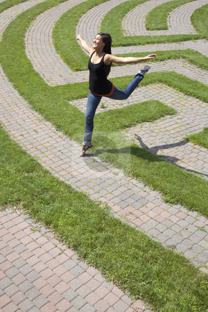 Young Woman Leaping Over a Grass Maze stock photo, Beautiful young Asian woman playfully jumps over the grass boundary of a park labyrinth. Vertical shot. by Edward Bock