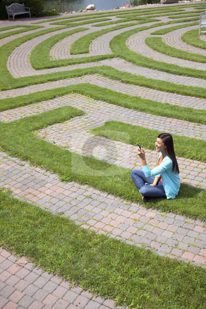 Young Woman Text Messaging in a Grass Maze stock photo, Beautiful young Asian woman laughs at a text message on her cellphone while sitting in a grass labyrinth. by Edward Bock