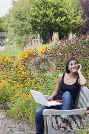 Young Woman Using Laptop and Cellphone on a Park Bench stock photo, Cute young woman smiles while seated on a park bench with a laptop and mobile phone. Trees and flowers are in the background. Vertical shot. by Edward Bock