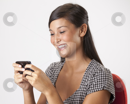 Young Woman Texting on a Cellphone stock photo, Beautiful young Asian woman smiles while writing a text message on her mobile phone. Horizontal shot. by Edward Bock