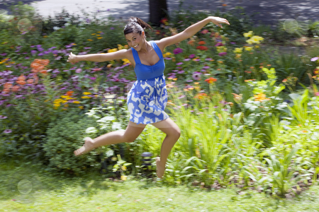Young Woman Frolicking on Grass stock photo, Beautiful young woman leaps on a grass lawn with bushes and flowers in the background. She is smiling at the camera. Horizontal shot. by Edward Bock