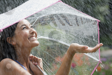 Young Woman Using an Umbrella in Rain stock photo, Beautiful young woman grins as she holds out her palm to catch falling water. She is holding an umbrella over her head. Horizontal shot. by Edward Bock