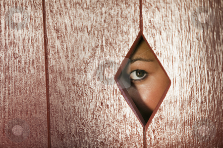 Woman Looking Through a Hole in the Wall stock photo, Woman peeks through a diamond shaped hole in a wall. Horizontal shot. by Edward Bock