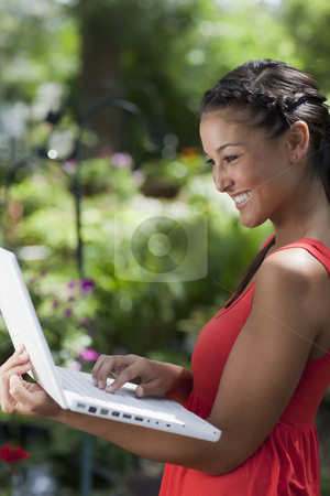 Young Woman Happily Working on a Laptop Outdoors stock photo, Attractive young Asian woman smiles while typing on a laptop in her arms. She is standing outdoors with a garden in the background. Vertical shot. by Edward Bock