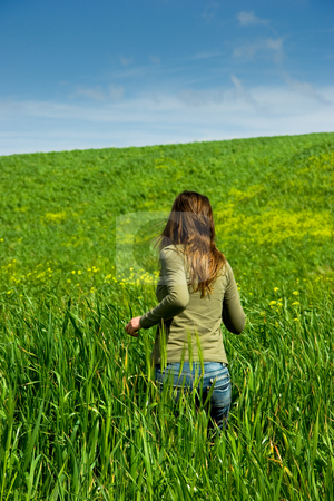 Running stock photo, Woman runing to inside of a green harvest field by ikostudio