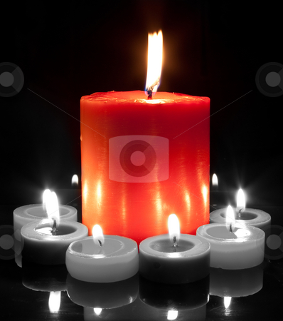 Large Red Candle - Black and White stock photo, A large red candle surrounded by small in black and white by Stephen Clarke