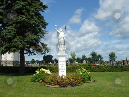White statue stock photo, White statue in front of a cemetery surrounded by green vegetation by Elenarts