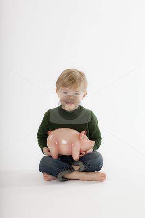 Young Boy Sitting with a Piggy Bank stock photo, Cute little boy sits cross-legged on the floor while holding a piggy bank. He is smiling towards the camera. Vertical shot. by Edward Bock