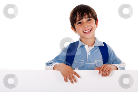 Boy standing behind the blank board stock photo, Young school kid standing behind the blank board isolated on white background by Get4net