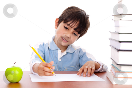 Cute young boy busy in drawing stock photo, Cute young boy busy in drawing with pile of books beside him by Get4net