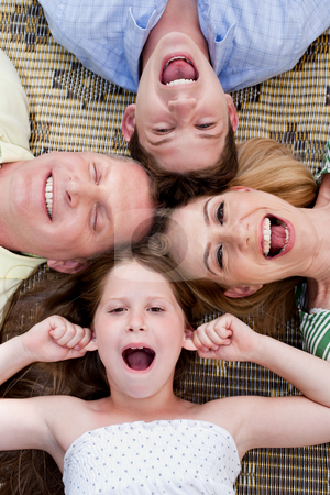 Happy family of four lying on the carpet with their heads together stock photo, Happy family of four lying on the carpet with their heads together and making fun towards the camera by Get4net