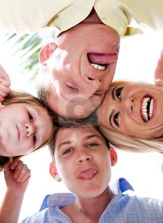 Joyful family making weird faces in huddle stock photo, Happy family of four in huddle making weird faces and smiling at camera by Get4net