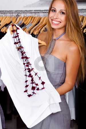 Happy woman at a retail shop stock photo, Young woman showing top to camera and smiling by Get4net