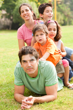 Affectionate family enjoying outdoors  stock photo, Portrait of a happy young family lying at the park on a summer day by Get4net