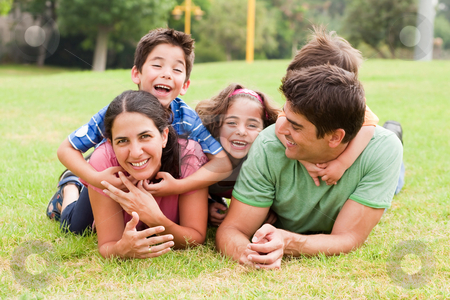 Playful family lying outdoors and smiling  stock photo, Playful family lying outdoors and smiling at camera during a sunny day by Get4net
