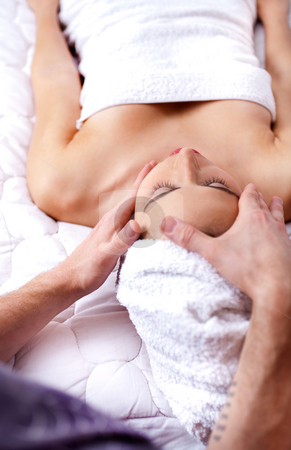 Young pretty woman getting face massage in spa  stock photo, Young pretty woman getting face massage in spa on the white bed with white turkey towel on her head by Get4net