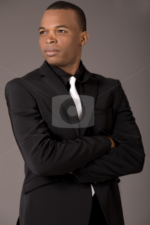 Young black american business man with folded hands stock photo, Young black american business man with folded hands on a grey background by Get4net
