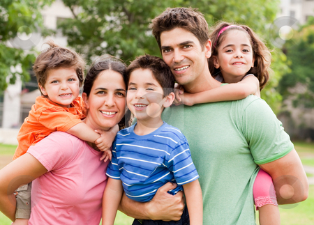 Caucasian parents piggyback their children stock photo, Young cacuasian parents piggyback their children as they smile at camera by Get4net