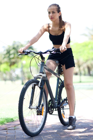 Young fitness woman on bicycle stock photo, Young fit and healthy woman on bicycle in vertical shot by Get4net