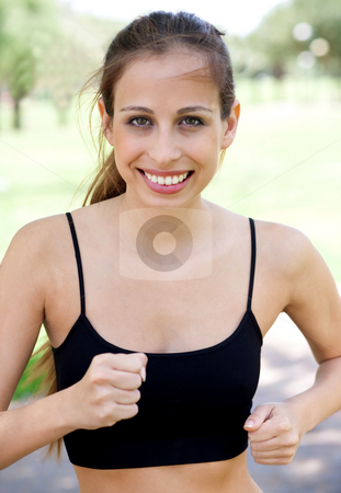 Smiling young woman running stock photo, Closeup portrait young smiling woman jogging over natural background by Get4net