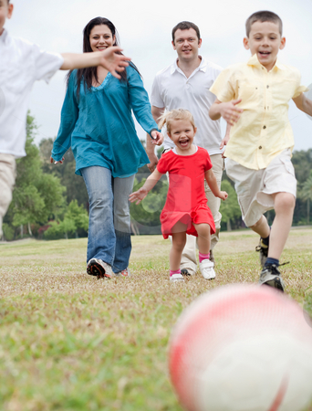 Sportive family playing football on the green lawn  stock photo, Sportive family playing football on the green lawn over natural background by Get4net
