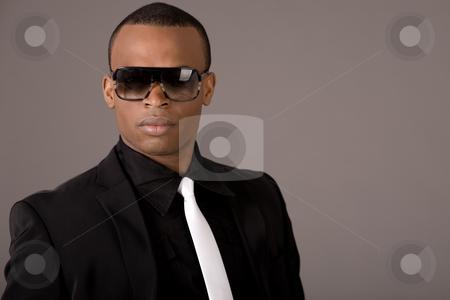 Ethnic young business man wearing sunglasses stock photo, Ethnic young business man wearing sunglasses indoor studio by Get4net