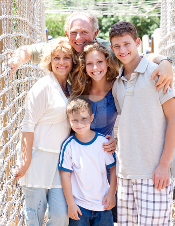 Portrait of family on hanging bridge stock photo, Closeup of happy family standing on a hanging bridge by Get4net