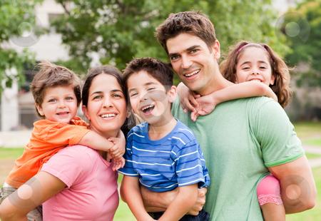 Piggyride time, kids enjoying stock photo, Caucasian parents piggyback their children, posing outdoors by Get4net