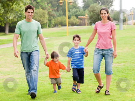 Happy family walking in the park stock photo, Happy family holding each others hand and walking in the park on a sunny afternoon by Get4net