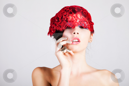 Beautiful Young Woman with a Lace Headpiece stock photo, A glamorous, high fashion woman looks at the camera while posing with red lace headpiece on her head and bare shoulders. Horizontal shot. by Angela Hawkey
