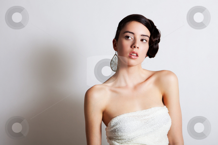 Elegant Young Woman Modeling a Dress stock photo, Beautiful young woman poses with an elegant hairstyle and strapless dress. She is looking pensively off to the side. Horizontal shot. by Angela Hawkey