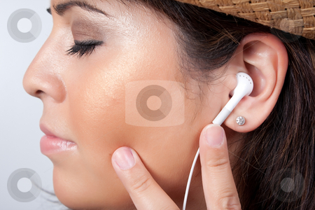 Stereo Earbud Headphones stock photo, An attractive Hispanic woman listening to and getting into the music playing through her stereo earbud headphones. by Todd Arena