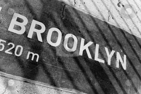Brooklyn Placard stock photo, A sign that reads BROOKLYN on a placard mounted in the concrete. You can see the shadows from the bridges wires. by Todd Arena