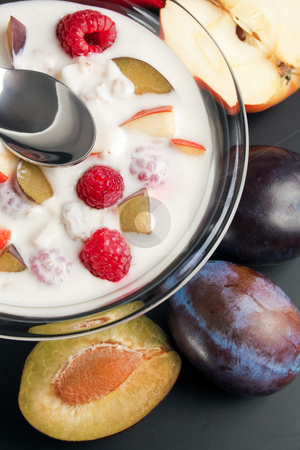 Yogurt mixed with fruit pieces stock photo, Glass bowl filled with yogurt mixed with fruit pieces arranged with spoon and some fruits around by Miroslav Ivanov
