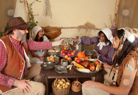 Thanksgiving dinner table stock photo, Reenactment scene of the first Thanksgiving Dinner in Plymouth in 1621 with a Pilgrim family and a Wampanoag Indian by Anneke