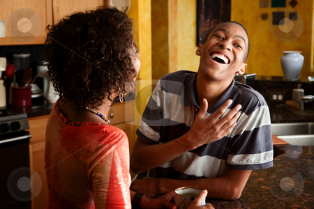African-American couple talks in kitchen stock photo, Attractive couple in kitchen by Scott Griessel